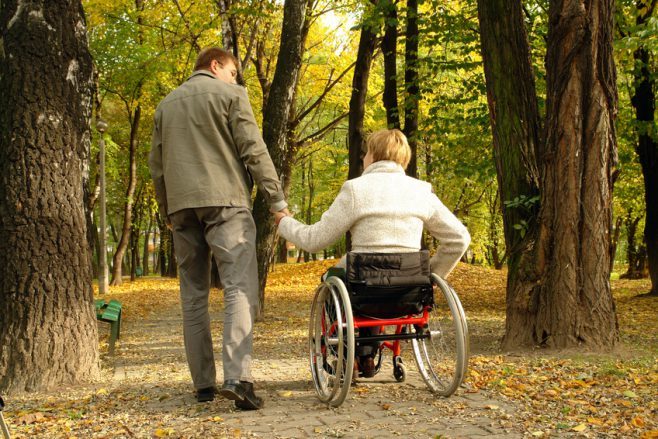 Husband and handicapped wife taking stroll in park alley