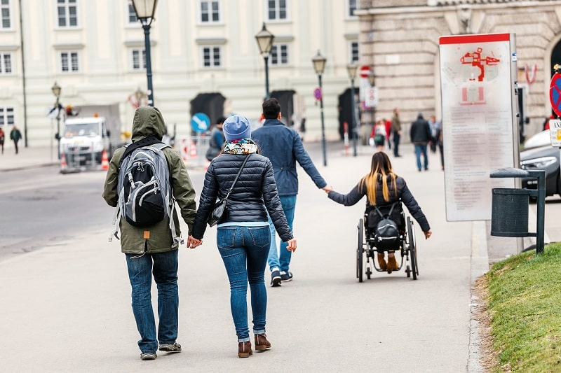 A man with a woman goes by the hand through the streets of Vienna against the background of another couple in love in a wheelchair, disabled love concept