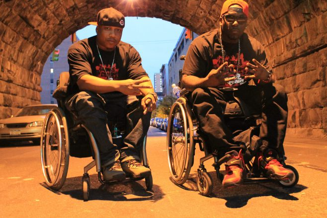 Rick Velasquez and Namel Norris, two men in their wheelchairs in a brick tunnel