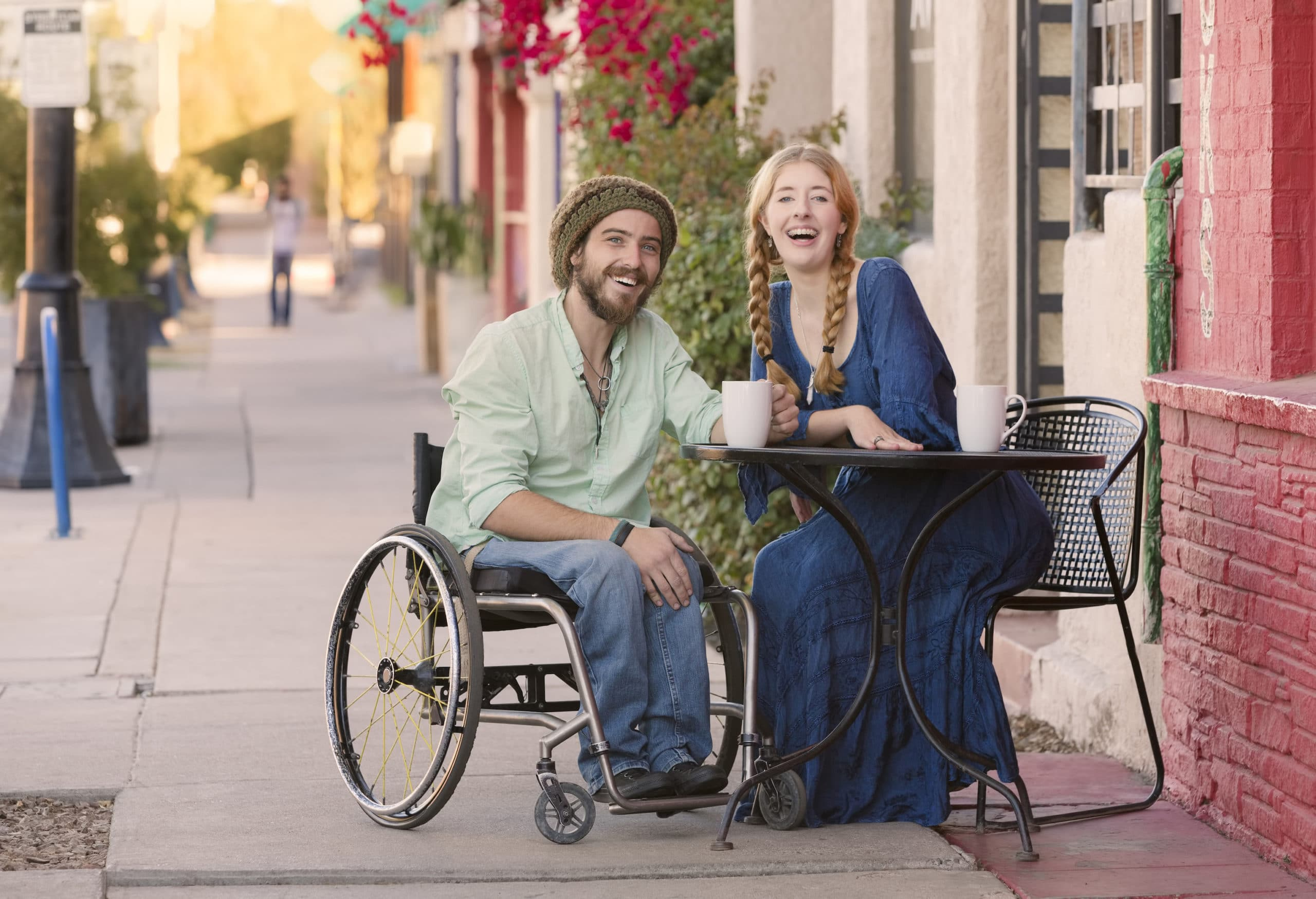 Woman and man in wheelchair having coffee at outdoor cafe table