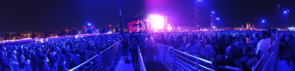 Nighttime festival with crowd of people. We see a ramp in the middle of the crowd and a lit up stage in the distance.