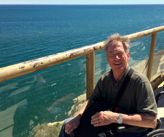 Jim Parsons sitting in his wheelchair above a turquoise body of water in Argentina's Port Loma.