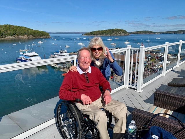Jim Parsons is sitting in his manual wheelchair wearing a read sweater and khaki pants. His wife is posing next to him for the photo. They are on an elevated area overlooking a harbor with many boats on the water.