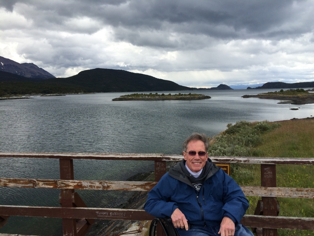 Jim Parsons sitting in his wheelchair with a lake and green hills in the background. The sky is cloudy, and Jim is wearing a blue jacket.
