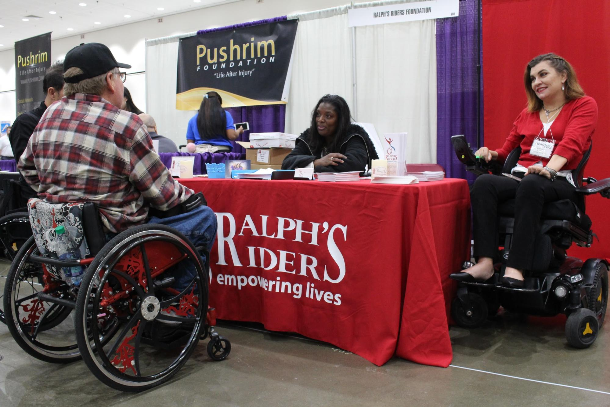 Marcy Lovett and Margarita Elizondo working the Ralph's Riders booth at Abilities Expo. A man in a wheelchair is visiting the booth.