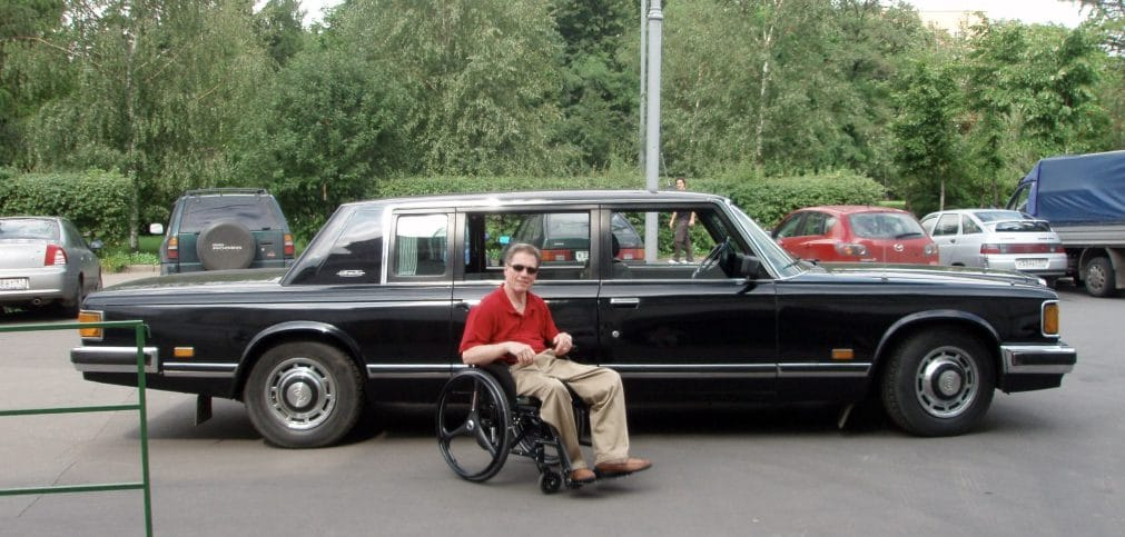 Jim Parsons is sitting in his manual wheelchair wearing a red polo shirt and khaki pants. He is in front of a long black limo-like car from the 70s or 80s.