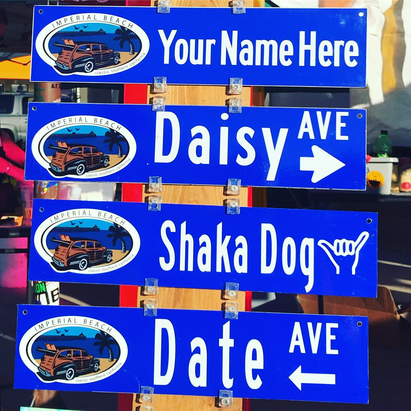 "Blue signs reading, ""Your Name Here,"" ""Daisy Ave,"" Shaka Dog,"" and Date Ave."""