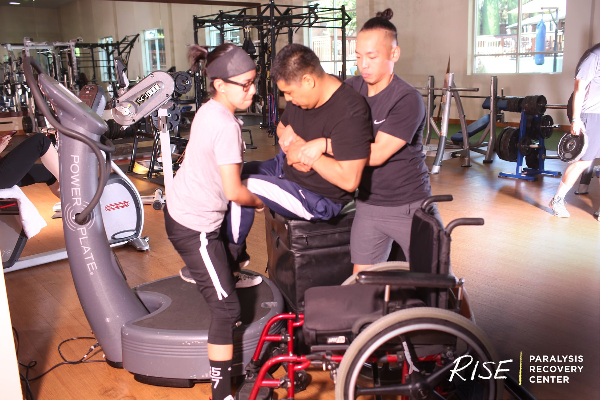 Two trainers help a man get out of his wheelchair onto a machine at the gym.