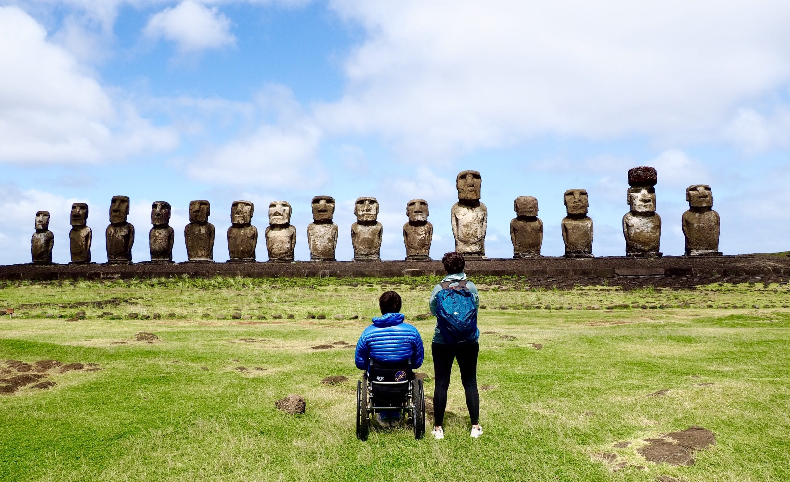 Pierre in his wheelchair and Myriam standing with their backs to the camera. They are looking at the statues of Easter Island.