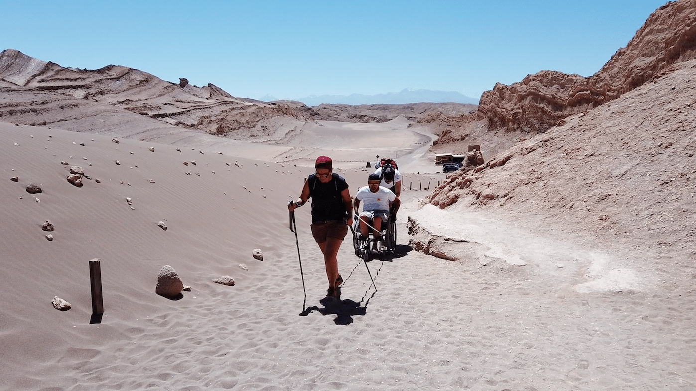 Myriam has walking sticks and ropes attached to Pierre and his chair behind her. Another man helps push Pierre in his chair up a sandy path in the Valley of the Moon in Chile.