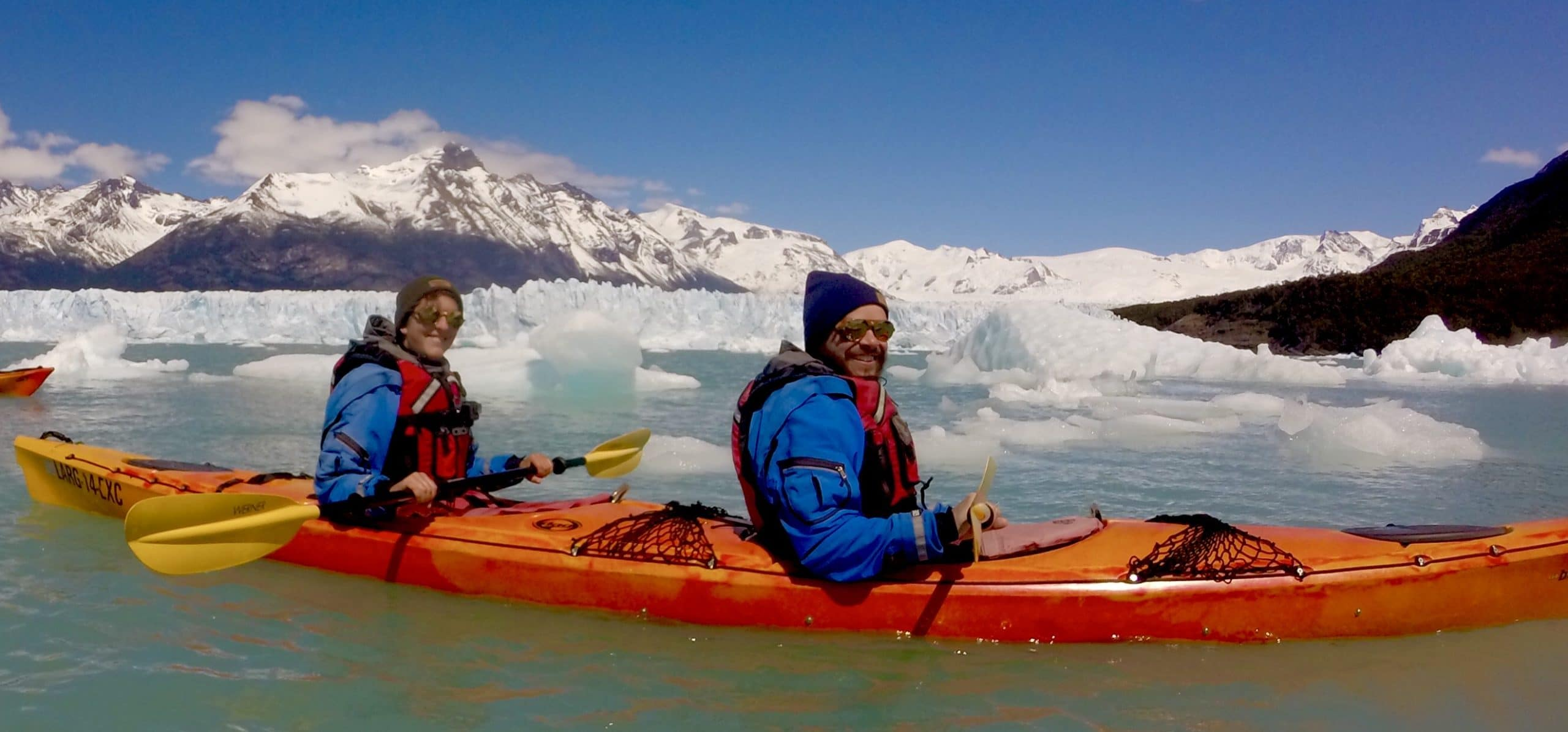Myriam on the back and Pierre on the front of an orange kayak. They are dressed warmly and the water is icy with snowy mountains in the background.