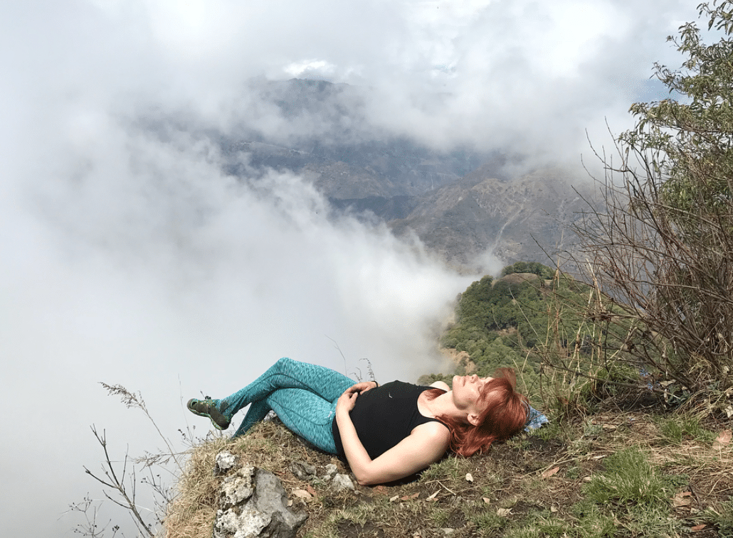 Erin Clark lies on the edge of a cliff. She is surrounded by clouds, but the sun is shining on her.