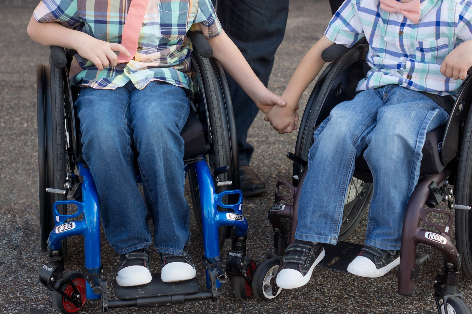Two boys from the chest down in wheelchairs holding hands.