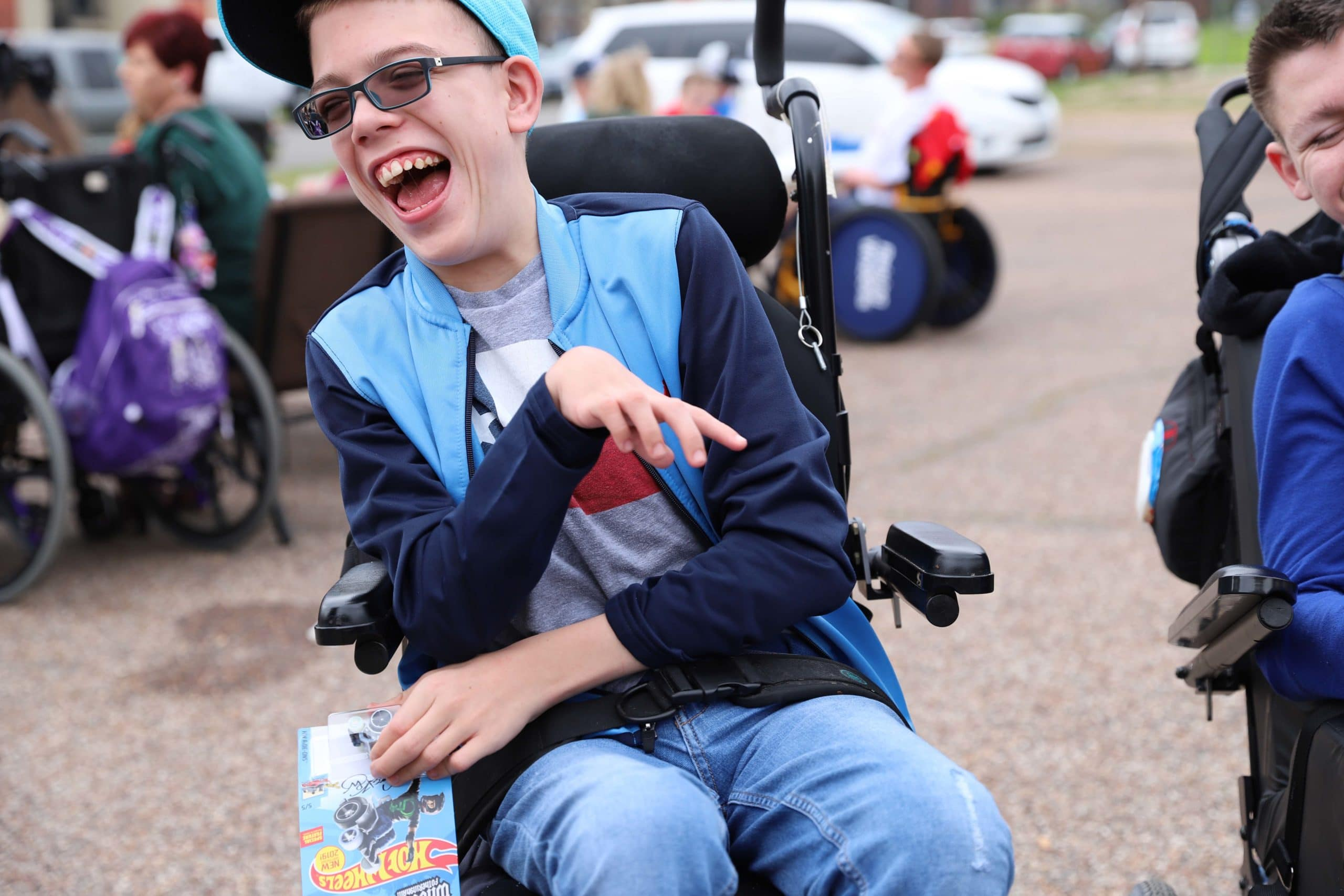 A boy in a power wheelchair wearing a baseball cap and sunglasses smiles large while looking off to his side.
